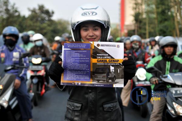 Petugas saat menunjukkan selebaran informasi mengenai perluasan sistem ganjil genap di Jakarta. Foto: RES