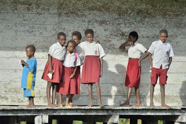 Kredit Editorial: Sergey Uryadnikov / Shutterstock.com. YOUW VILLAGE, ATSY DISTRICT, ASMAT REGION, IRIAN JAYA, NEW GUINEA, INDONESIA - MAY 23, 2016: Schoolchildren in uniform. Small village of the Asmat tribe.  New Guinea.May 23, 2016